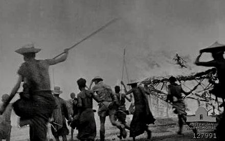 55e6ec9b7b311_MEMBERS-OF-THE-22ND-AUSTRALIAN-INDEPENDENT-COMPANY-ASSISTED-BY-FRIENDLY-NATIVES-BURN-DOWN-PRO-JAPANESE-NATIVES-HUTS..jpg