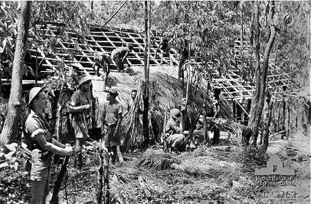 Rocky Williams foreground stands guard while Timorese natives build a bamboo hut