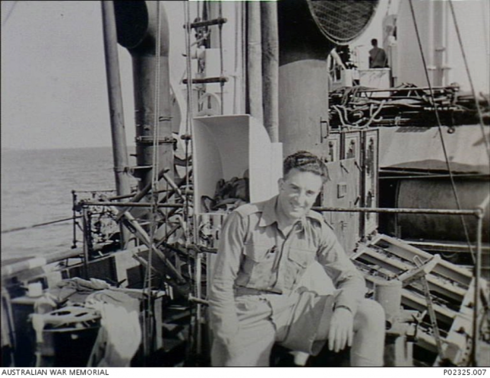 P02325.007 – c. September 1945 - Arafura sea.  Informal outdoor portrait of Sergeant Keith B. Davis, Military History Section (MHS) official photographer, sitting on the deck of HMAS Parkes.png